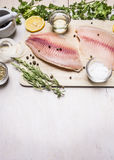 Raw fillet of tilapia with spices and herbs, lemon and pepper on a cutting board a white background rustic village Stock Photo