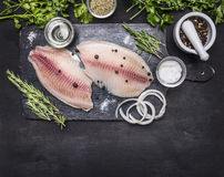 Raw fillet of tilapia with spices and herbs, lemon and pepper on a cutting board on  white background rustic village top view. Raw fillet of tilapia with spices Royalty Free Stock Image
