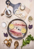 Raw fillet of tilapia spices and herbs, lemon and pepper, onion, parsley, rosemary on a pan  white background rustic back Royalty Free Stock Photography