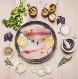 Raw fillet of tilapia with spices and herbs, lemon and pepper on a pan on  white background rustic background top view Stock Image
