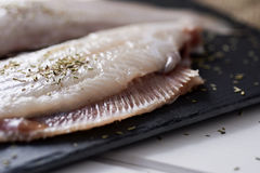Raw filleted common sole. Closeup of a pair of raw filleted common sole on a slate tray placed on a rustic wooden table Stock Photography