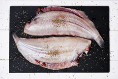 Raw filleted common sole. High-angle shot of a pair f raw filleted common sole on a slate tray placed on a rustic wooden table Royalty Free Stock Photo