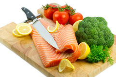 Raw fish. Isolated fresh raw red fish with lemon, broccoli, greenery and tomatoes on the wooden cutting board Royalty Free Stock Photos