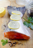 Raw fish. Raw salmon and lemon on wooden board Royalty Free Stock Photo