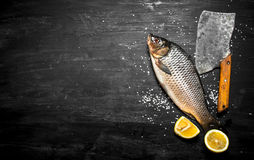 Raw fish with an axe. On a black wooden background Stock Photography