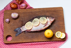 Raw fish carp on Boards for cutting. Fresh carp with spices, lemon slices and onions on a cutting board close-up Stock Photos