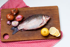 Raw fish carp on Boards for cutting. Fresh carp with spices, lemon slices and onions on a cutting board close-up Stock Image