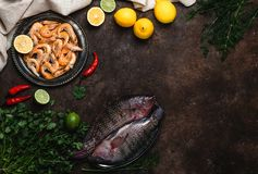 Raw fish, chili peppers, shrimp, herbs with lemons and tablecloth Royalty Free Stock Photos