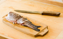 Raw fish on cut board with knife in kitchen Royalty Free Stock Photography