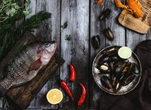 Raw fish on cutting board and mussels with lime on rustic wooden table. Top view of raw fish on cutting board and mussels with lime on rustic wooden table Stock Photos