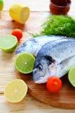 Raw fish dorado on board. Food closeup Royalty Free Stock Photos