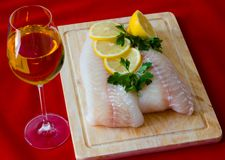 Raw fish fillet. With lemons on red Stock Image