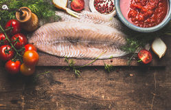 Raw fish fillet with frish herbs, tomatoes and sauce on dark rustic cutting board on dark aged wooden background, top view, border. Pollack fish cooking Stock Photography