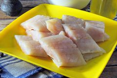 Raw fish fillets, flour and eggs. Pollock raw sliced fish and other ingredients royalty free stock photos