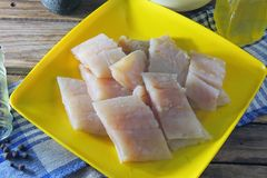 Raw fish fillets, flour and eggs. Pollock raw sliced fish and other ingredients royalty free stock photography