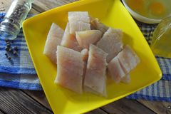 Raw fish fillets, flour and eggs. Pollock raw sliced fish and other ingredients stock photos