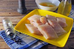 Raw fish fillets, flour and eggs. Pollock raw sliced fish and other ingredients royalty free stock images