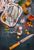 Raw fish fillets with kitchen knife , spices and cut vegetables, cooking preparation on dark rustic background. Top view Royalty Free Stock Images