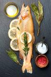 Raw fish golden trout with herbs and spices Royalty Free Stock Image