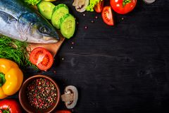 Raw fish and ingredients: lemon, spices, greens, tomato, on a wooden table, top view. Preparation of sea fish, free space royalty free stock image