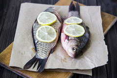 Raw fish with lemon on a cutting board Royalty Free Stock Photos