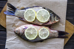 Raw fish with lemon on a cutting board Royalty Free Stock Images