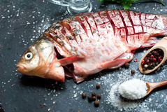 Raw fish with lemon, herbs and spices on dark vintage background. Delicious fresh fish on dark vintage background. Fish with aromatic herbs, spices and Stock Photos