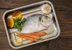 Raw fish on wooden back  ground. Raw fish with lemon in kitchen before cooking Stock Images