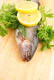 Raw fish with lemon and parsley. On wooden background Stock Photo