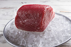 Raw fish meat on ice. Red meat lying on plate. Basic ingredient for sushi. Thick and juicy Stock Images