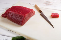 Raw fish meat and knife. Fish meat on cooking board. Fresh salmon for uramaki rolls. Calories and protein Royalty Free Stock Photos