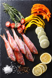 Raw fish red mullet with vegetables and lemon on the table. Vert Royalty Free Stock Image