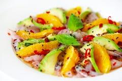 Raw fish salad carpaccio with avocado and orange slices. Black sesame seeds and chili Royalty Free Stock Photo