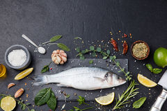 Raw fish, sea bass on slate black board Top view. Raw fish, sea bass on slate black board. Ingredients for cooking, grill, roasting. Top view Copy space Royalty Free Stock Image