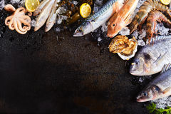 Raw Fish and Seafood Chilling on Ice on Wood Table. High Angle Still Life View of Variety of Raw Fish and Seafood Chilling on Ice with Lemon and Arranged Around Stock Photos