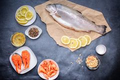 A brown craft paper with raw fish, lemon slices of salmon shrimp on a white plate, lemon, pepper and salt is placed on a dark gray royalty free stock image
