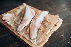 Raw fish slices, knife on cutting board, top view Stock Photo