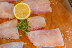 Raw fish slices with lemon on wooden cutting board Royalty Free Stock Photography