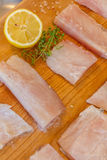 Raw fish slices with lemon on wooden cutting board. Fresh raw fish slices with lemon on wooden cutting board Stock Photo