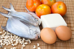 Raw fish with some of protein foods. Raw fish with eggs, toufu, black eye beans and tomatoes indicating healthy eating habits Royalty Free Stock Image