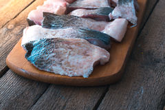 Raw fish with spices on a wooden board. stock photo