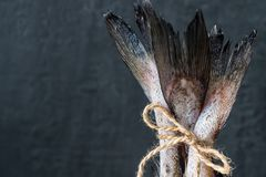 Raw fish tails tied with rope with bow on dark background. Selective focus.  Royalty Free Stock Images