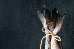 Raw fish tails tied with rope with bow on dark background. Selective focus.  Royalty Free Stock Photo