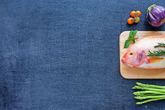 Raw fish and vegetables on a dark table Royalty Free Stock Images