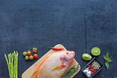 Raw fish and vegetables on a dark table Stock Photography