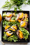 Raw fish with vegetables and herbs on the pan. Raw fish on the pan Stock Image