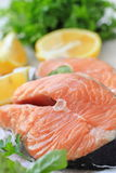 Raw fish with vegetables and lemon prepared for cooking. Raw salmon fillet with vegetables and lemon prepared for cooking Royalty Free Stock Photography