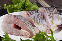 A raw fish. On the white plate Stock Photos