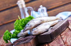 Raw fish. On wooden board and on a table Royalty Free Stock Image
