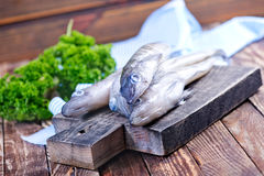 Raw fish. On wooden board and on a table Stock Images